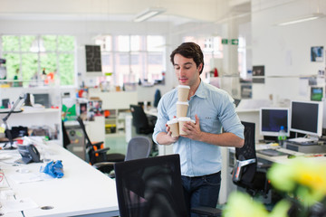 Businessman balancing coffee cups