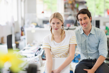 Smiling man and woman sitting in office