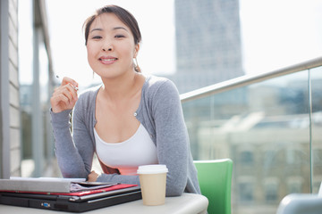 Smiling businesswoman working on urban balcony