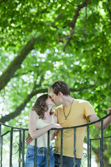 Couple hugging and kissing near railing outdoors