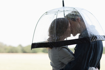 Couple in rain kissing underneath umbrella