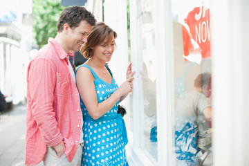 Couple looking at merchandise in store window together
