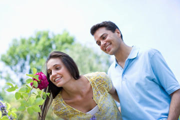 Smiling couple smelling red rose in park