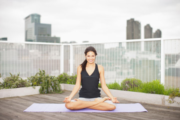 Woman practicing yoga on rooftop deck