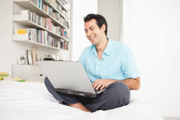 Man sitting on bed using laptop