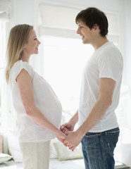 Husband and pregnant wife holding hands face to face