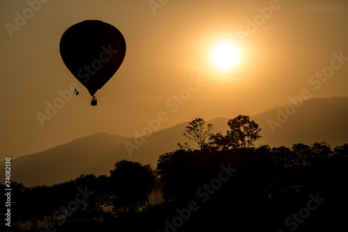 Fotobehang Ballon Hot air balloon fly up in the air with silhouette environment