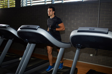 Fit man running in a gym on a treadmill focused looking away