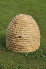 A Wicker Made Natural Material Beehive on Grass.