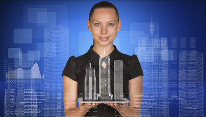 Beautiful businesswoman holding tablet pc with layouts on it.
