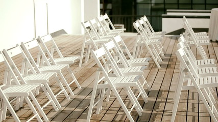A lot of white wooden chairs on the wooden floor