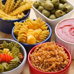 Variety of uncooked italian pasta on wooden table