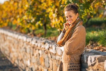 Portrait of happy young woman in autumn park