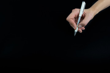 Hand holding pencil isolated on black background