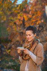 Happy young woman in autumn evening outdoors writing sms
