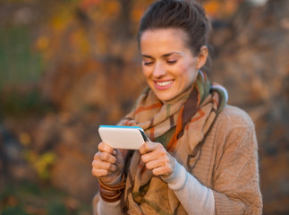 Closeup on young woman in autumn evening outdoors writing sms