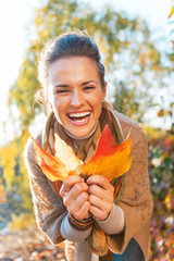 Portrait of happy young woman with autumn leafs outdoors