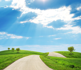 Road running through green hills