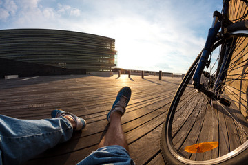 cyclist sitting resting with mountain bike at sunset, POV