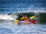 Kayak surfing on rough sea