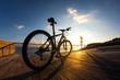 Leinwandbild Motiv silhouette of  sportsman and mountain bike at the sunset