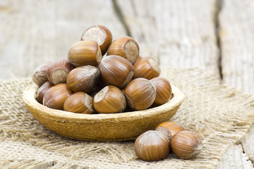 hazelnuts in a bowl on old wooden background