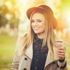 Cute young woman with takeaway coffee outdoors in fall