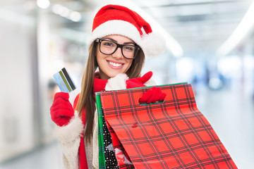 Cheerful young woman in mall shopping for Christmas