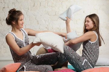 Twin sisters with pillows in the bedroom