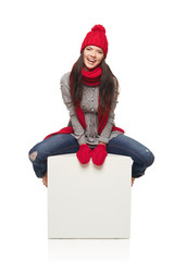 Winter woman sitting on big white box with copy space