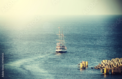 Vintage picture of old sailing ship leaving port.
