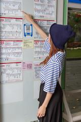 Woman at bus stop looking at timetable
