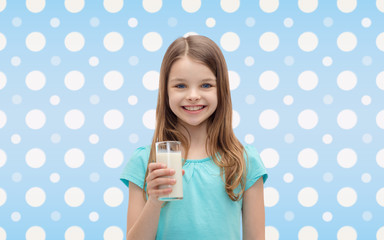 smiling girl with glass of milk over polka dots