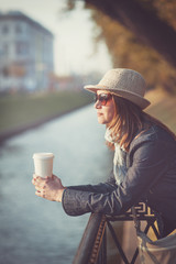 Beautiful woman in hat and scarf with cup of coffee
