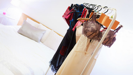 Various lingerie and clothing on a hanger rack in bedroom