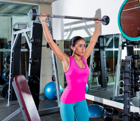 brunette girl wide grip barbell shoulder press gym