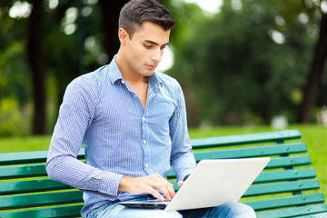 Young man using a laptop computer outdoors