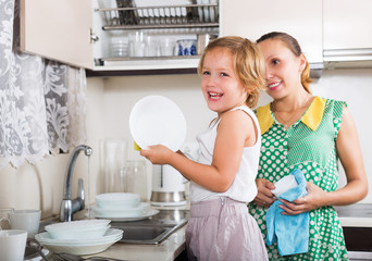 Happy daughter with mother washing plates