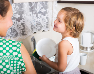 Baby with woman washing plates