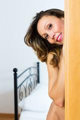 Naked woman posing in doorway