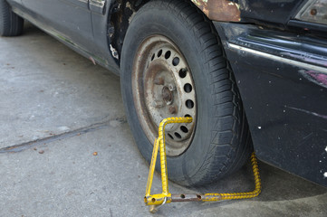 Old vehicle is immobilised by yellow wheel clamp, on road.