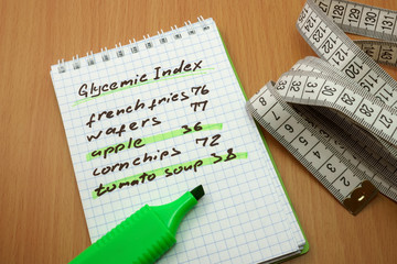 Measuring tape, a marker and a notepad with a glycemic index