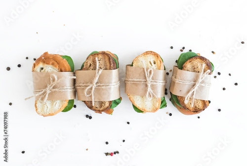 Chicken and spinach sandwiches wrapped in craft paper over a whi - 74097988