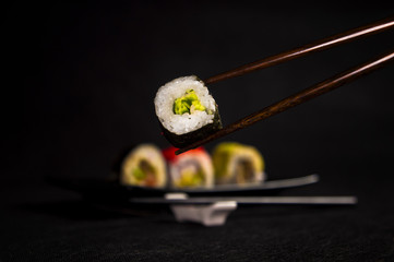 Sushi on black background, japanese cuisine, chopsticks