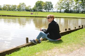 Frau sitzt an einem Teichufer