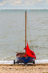 Blue sailing dinghy, boat on a beach with a red sail