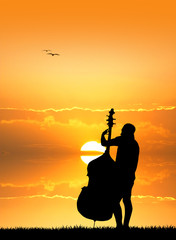 man with cello at sunset