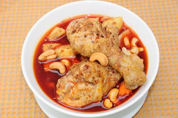 Chicken Mussaman Curry on orange plate mat.