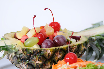 Fruits salad in pineapple on white plate, food stylist