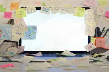 Office desk with laptop covered by post it papers